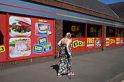Woman using a walking stick as she walks past an Iceland shop showing cheap offers on its window in Kings Heath on 14th April 2020 in Birmingham, England, United Kingdom. Iceland Foods Ltd is a British supermarket chain. It has an emphasis on the sale of frozen foods, including prepared meals and vegetables. They also sell non-frozen grocery items such as produce, meat, dairy, and dry goods, and is known for being a low cost, budget option for food.