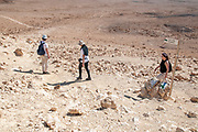 "A group of hikers hiking in Makhtesh Ramon a geological feature of Israel's Negev desert. Located at the peak of Mount Negev, the world's largest ""erosion cirque"" (steephead valley or box canyons). The formation is 40 km long, 2–10 km wide and 500 meters deep, Today the area forms Israel's largest national park, the Ramon Nature Reserve."