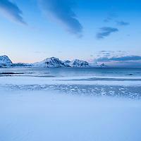 Snow covers Haukland beach, Lofoten Islands, Norway