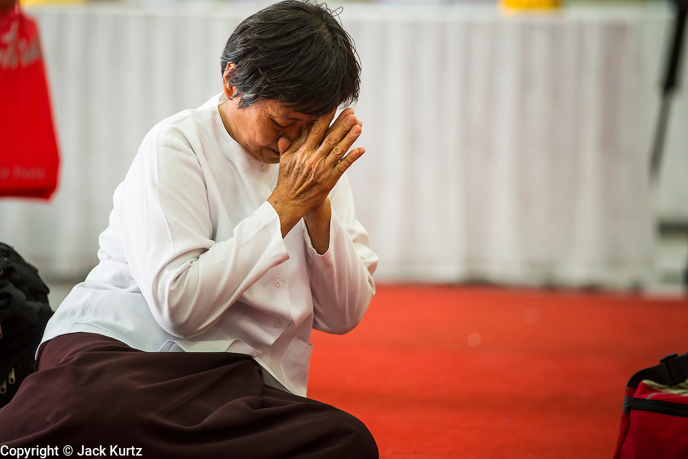 26 NOVEMBER 2012 - BANGKOK, THAILAND:  A woman prays for the hospitalized King of Thailand at Siriraj Hospital in Bangkok. Siriraj was the first hospital in Thailand and was founded by King Chulalongkorn in 1888. It is named after the king's 18-month old son, Prince Siriraj Kakuttaphan, who had died from dysentery a year before the opening of the hospital. It's reported to one of the best hospitals in Thailand and has been home to Bhumibol Adulyadej, the King of Thailand, since 2009, when he was hospitalized to treat several ailments. Since his hospitalization tens of thousands of people have come to pay respects and offer get well wishes. The King's 85th birthday is on Dec 5 and crowds at the hospital are growing as his birthday approaches. The King is much revered throughout Thailand and is seen as unifying force in the politically fractured country.       PHOTO BY JACK KURTZ