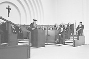 Nederland, Nijmegen, 28-12-1983 Een promotie in de oude aula van de Katholieke Universiteit Nijmegen, KUN, die later Radboud Universiteit, RU, ging heten. Aan de muur hangt een kruisbeeld vanwege het katholieke karakter van de instelling. Rechts de pedel met zijn staf .Foto: ANP/ Hollandse Hoogte/ Flip Franssen