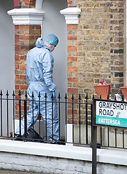 © Licensed to London News Pictures. 15/08/2018. London, UK. An investigator in a protective suit enters a house where a woman has been stabbed to death in Battersea, South London. A 40 year old male was arrested at the scene on suspicion of murder. Photo credit: Peter Macdiarmid/LNP