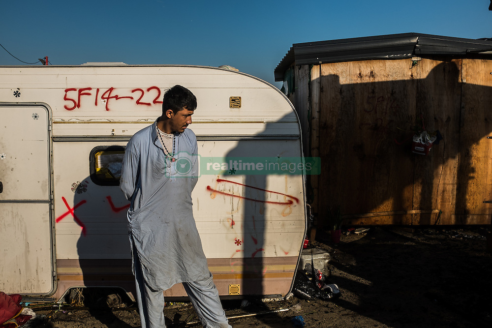 October 25, 2016 - Calais, France - A Migrant stand during the eviction of the Calais Jungle in front of a Caravan  in Calais, France, on 25 October 2016. Up to the evening, about 4,000 migrants from the Refugee camp on the coast at the English Channel were distributed to several regions in France. The police have begun to tear down the huts and tents in the camp. (Credit Image: © Markus Heine/NurPhoto via ZUMA Press)