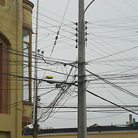 A tangle of electric and telephone wires crowd a power pole in Punta Arenas, Chile.