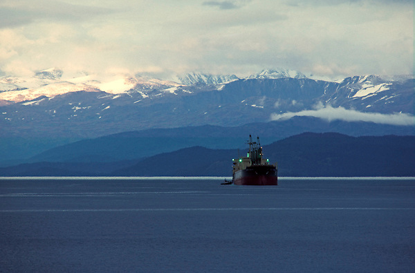 Tanker passing through calm waters along a snow covered mountainous landscape
