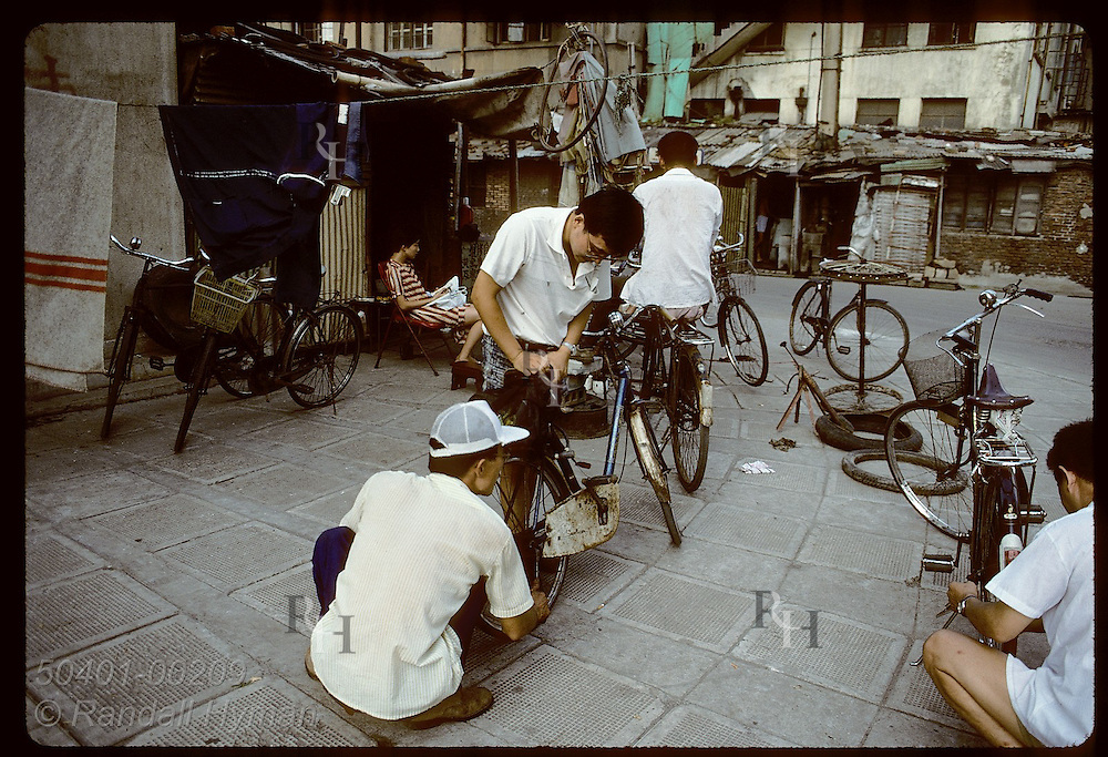 Neighborhood bike repair shop operates on a street corner in a poor industrial area of Shanghai China