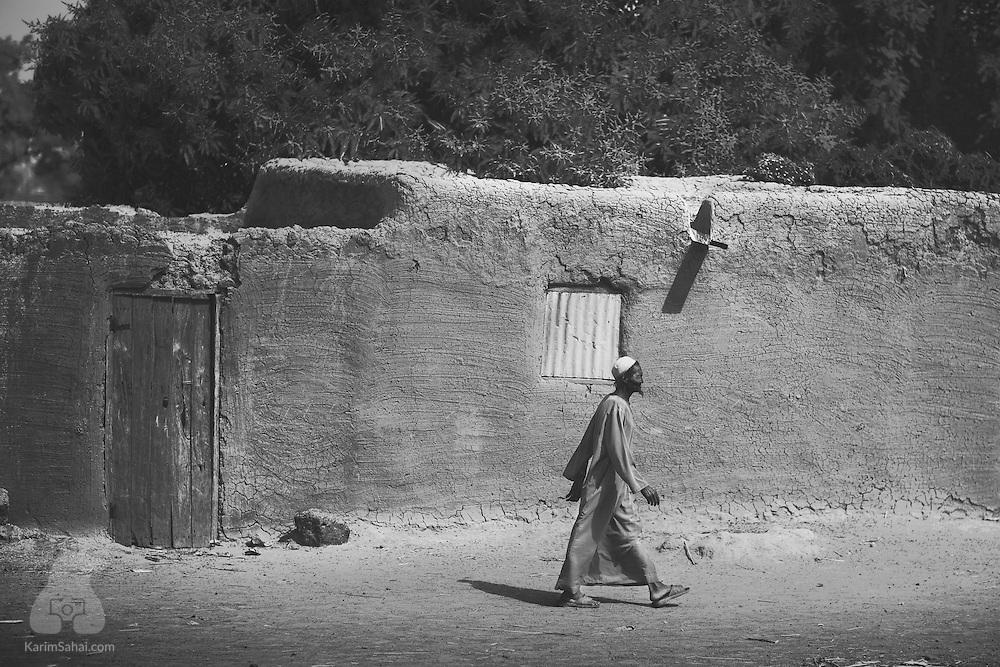 A man wearing a traditional qamis (robe) walks past a mudhouse near Ségou, Mali.