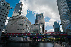 © Licensed to London News Pictures. 23/08/2012, London, UK.  A DLR train crosses a dock at Canary Wharf financial district in east London, Thursday, Aug. 23, 2012. DLR, Docklands Light Railway, celebrates its 25th annivesary today. Photo credit : Sang Tan/LNP