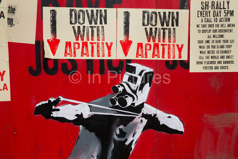 """Glastonbury Festival, 2015. Shangri La is a festival of contemporary performing arts held each year within Glastonbury Festival. The theme for the 2015 Shangri La was Protest. <br /> Billboard in Shangri La with demonstrator stencil in front of """"Down with apathy"""" posters"""