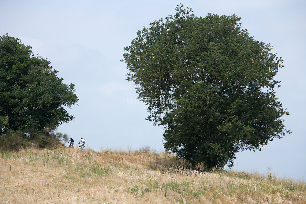 two cyclist pedaling uphill in the countryside