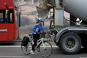 Woman cyclist starts to overtake a stationary cement mixer lorry in Shoreditch, London. Watching oncoming traffic and trying to predict the movements of this industrial vehicle, the lady rider pushes off the ground and tries to get past the truck to gain advantage. So far in 2015, of the 6 cyclists killed, 5 have been women and all involving heavy lorries.
