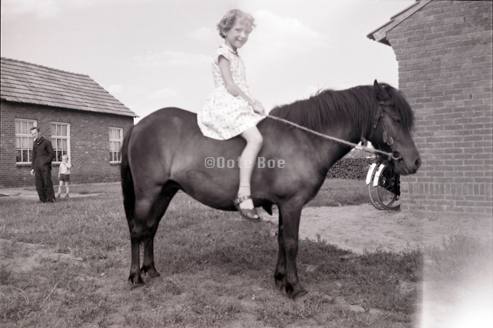 a young girl sitting on the back of a pony with father looking on Holland