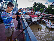 "20 JUNE 2017 - BANGKOK, THAILAND:   Men fish from the deck of the Krung Thon Bridge with homes scheduled for demolition in a community along the Chao Phraya River south of Krung Thon Bridge. This is one of the first parts of the riverbank that is scheduled to be redeveloped. The communities along the river don't know what's going to happen when the redevelopment starts. The Chao Phraya promenade is development project of parks, walkways and recreational areas on the Chao Phraya River between Pin Klao and Phra Nang Klao Bridges. The 14 kilometer long promenade will cost approximately 14 billion Baht (407 million US Dollars). The project involves the forced eviction of more than 200 communities of people who live along the river, a dozen riverfront  temples, several schools, and privately-owned piers on both sides of the Chao Phraya River. Construction is scheduled on the project is scheduled to start in early 2016. There has been very little public input on the planned redevelopment. The Thai government is also cracking down on homes built over the river, such homes are said to be in violation of the ""Navigation in Thai Waters Act."" Owners face fines and the possibility that their homes will be torn down.              PHOTO BY JACK KURTZ"