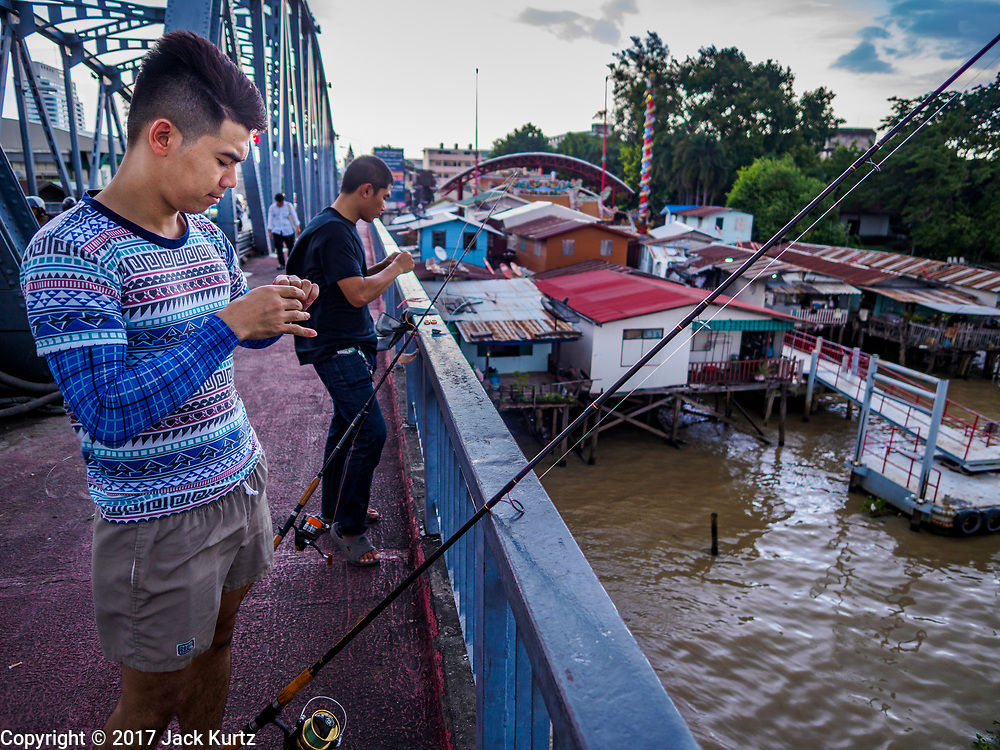 """20 JUNE 2017 - BANGKOK, THAILAND:   Men fish from the deck of the Krung Thon Bridge with homes scheduled for demolition in a community along the Chao Phraya River south of Krung Thon Bridge. This is one of the first parts of the riverbank that is scheduled to be redeveloped. The communities along the river don't know what's going to happen when the redevelopment starts. The Chao Phraya promenade is development project of parks, walkways and recreational areas on the Chao Phraya River between Pin Klao and Phra Nang Klao Bridges. The 14 kilometer long promenade will cost approximately 14 billion Baht (407 million US Dollars). The project involves the forced eviction of more than 200 communities of people who live along the river, a dozen riverfront  temples, several schools, and privately-owned piers on both sides of the Chao Phraya River. Construction is scheduled on the project is scheduled to start in early 2016. There has been very little public input on the planned redevelopment. The Thai government is also cracking down on homes built over the river, such homes are said to be in violation of the """"Navigation in Thai Waters Act."""" Owners face fines and the possibility that their homes will be torn down.              PHOTO BY JACK KURTZ"""