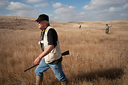 Experienced hunter Byron Grubb out with fellow hunters Timmy Stein and John Davidson on the North Dakota prairie grasslands shooting upland game birds such as grouse near Minot, North Dakota, United States. Byron has been shooting for most of his life and puts considerable efforts into his hunting, efforts which reward him with wild game meats, none of which is wasted.