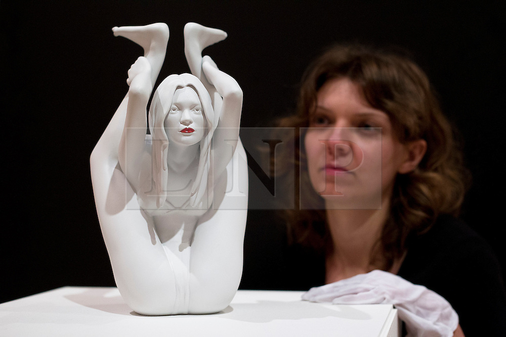 © Licensed to London News Pictures. 08/10/2012. LONDON, UK. A member of Bonhams staff looks at 'Cayratid' (2008) a sculpture of model Kate Moss in a yoga position by artist Marc Quinn (est. GB£50,000-70,000) ahead of a sale at the auction house's New Bond Street premises. The auction, featuring a collection of contemporary art and design is set to take place on Thursday the 11th of October at Bonham's New Bond Street auction house. Photo credit: Matt Cetti-Roberts/LNP