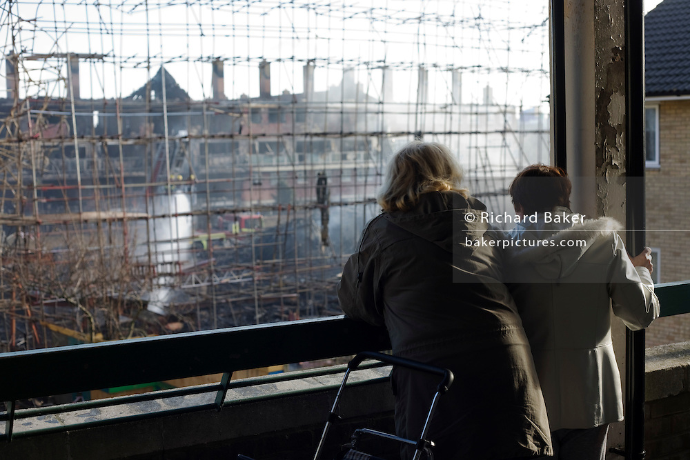 Two local women look at the devastation of a construction site after an inner-city estate fire in south London. About 310 people were forced to leave their homes after the fire engulfed a wooden structure under construction in scaffolding at Sumner Road and Garrisbrooke Estate, Peckham, London at about 0430 AM. It spread to two blocks of maisonettes and a destroyed a pub. More than 150 firefighters tackled this unusually large and ferocious fire which injured ten people, including two police officers who received hospital treatment for minor injuries.  .