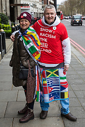 London, UK. 16th March, 2019. A couple prepare to join thousands of people marching through central London on the March Against Racism demonstration on UN Anti-Racism Day against a background of increasing far-right activism around the world and a terror attack yesterday on two mosques in New Zealand by a far-right extremist which left 49 people dead and another 48 injured.