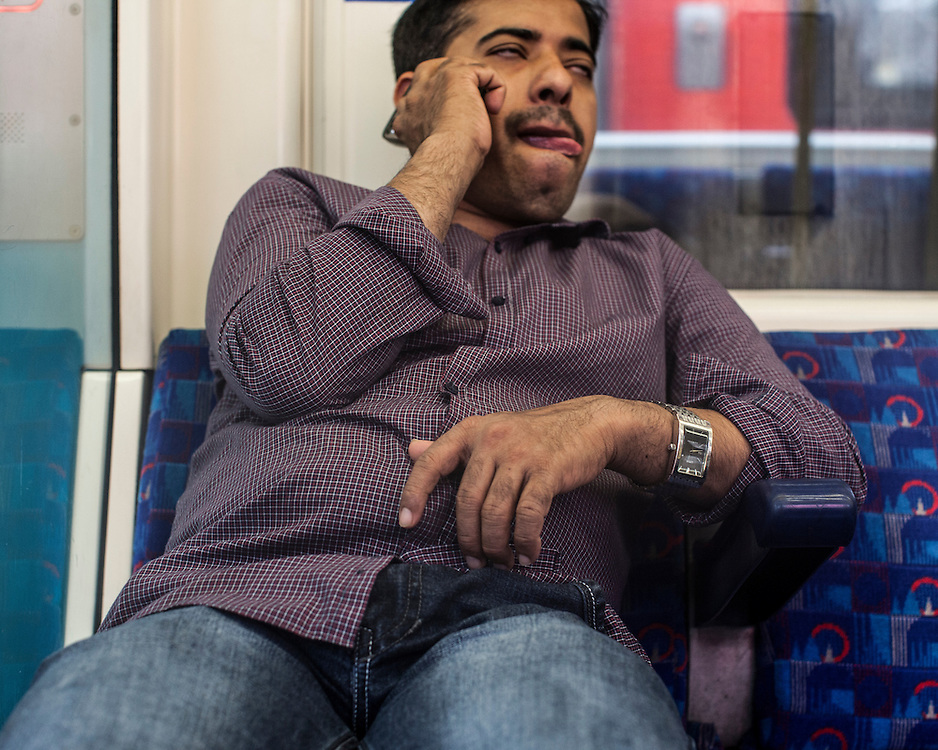 Asian man on the phone on the London Underground
