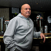 Customer leaning on the bar at Parson Cross pub, Sheffield, South Yorkshire, UK