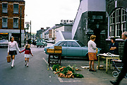 Small street market selling carrots people and traffic in Macroom, County Cork, Republic of Ireland in 1969