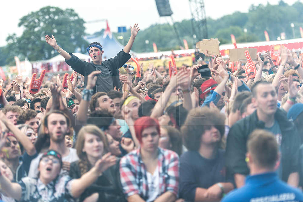 © Licensed to London News Pictures. 30/08/2015. Reading, UK. Festival goers watch The Maccabees performing at Reading Festival 2015, Day 3 Sunday, shrouded in stage effects smoke.  In this picture - Hugo White.  Photo credit: Richard Isaac/LNP
