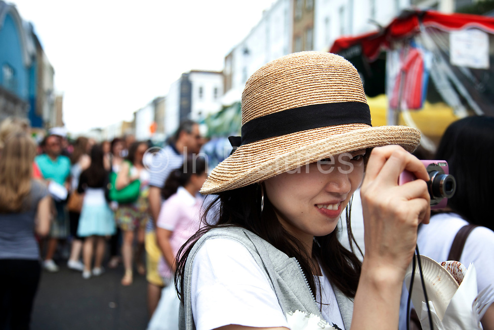 A Japanese woman takes a picture on Portobello Road market, Notting Hill, West London. This famous Saturday market is when the antique stalls line the streets as well as the food stalls further down the hill. This is classic London with busy crowds of people coming to hang out, maybe buy something, or just browse the stalls and have some food.