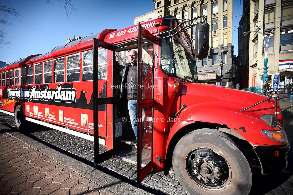 Nederland, Amsterdam , 2 februari 2012..Erik de Visser (in de bus) van Tours en Tickets op het Damrak..Foto:Jean-Pierre Jans