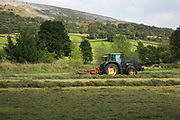 Farmer using a tractor to gather hay on the last day before rain is expected in his field in Reeth at Swaledale. Yorkshire, England, UK. This is a farming area where rural living and the countryside is at the centre of life in this county. Swaledale runs broadly from west to east. To the south and east of the ridge a number of smaller dales. Swaledale is a typical limestone Yorkshire dale, with its narrow valley-bottom road, green meadows and fellside fields, white sheep and dry stone walls on the glacier-formed valley sides, and darker moorland skyline.