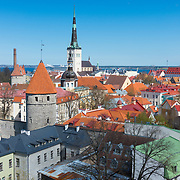 Iconic view of Tallinn old town with city wall towers, Oleviste church and red roofs