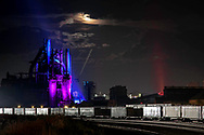 The moon rises over the remains of the Bethlehem Steel plant as an incoming NS #T12 train illuminates the yard full of inter-model cars. Not long ago, this facility was one of the largest producers of steel in the world, but is now in the process of transformation into the Sands Casino Resort. The blast furnace has been saved as a piece of sculpture to show the heritage of the place and add to the casino's theme.