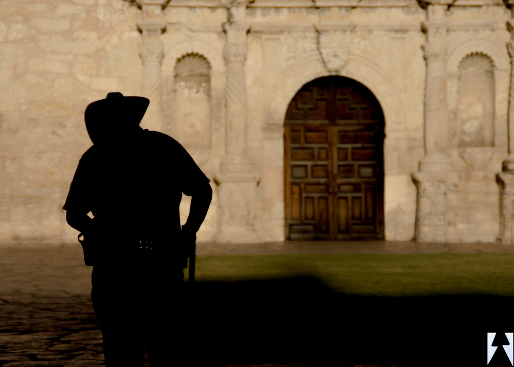 Three quarter silhouette shot of a San Antonio police officer from behind with the partial façade and front doors of the Alamo in the background.