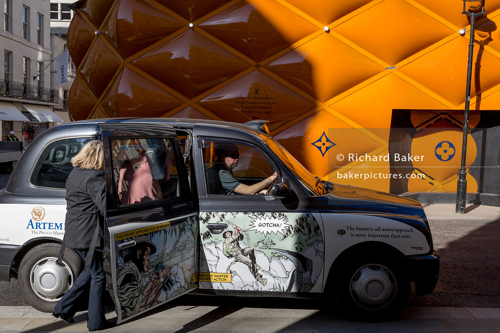 A black cab picks up fares opposite the temporary renovation hoarding of luxury brand Louis Vuitton in New Bond Street, on 25th February 2019, in London, England.