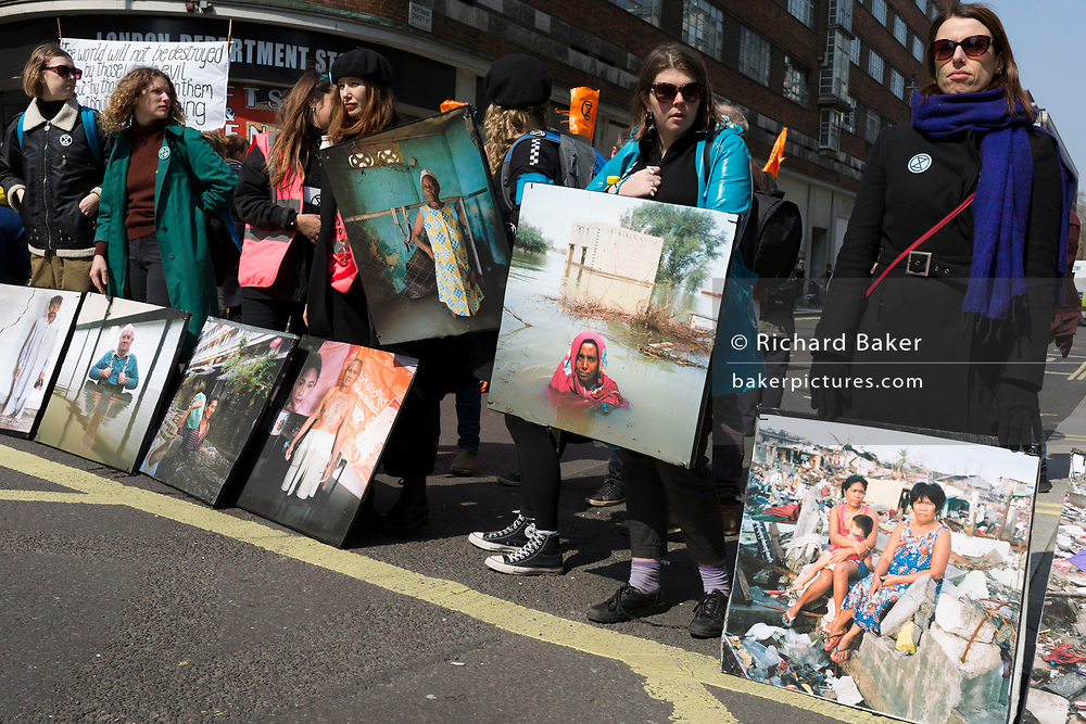 Using some portraits from the project 'Drowning World by photographer Gideon Mendand some of his flood victim portraits 'Drowning World' during the climate Change protest with Extinction Rebellion blocking Oxford Street and simultaneously stop traffic across central London including Marble Arch, Piccadilly Circus, Waterloo Bridge and roads around Parliament Square, on 15th April 2019, in London, England.