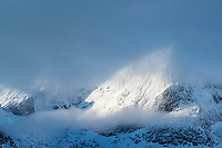 Snow covered mountain emerges from clouds, Flakstadøy, Lofoten Islands, Norway
