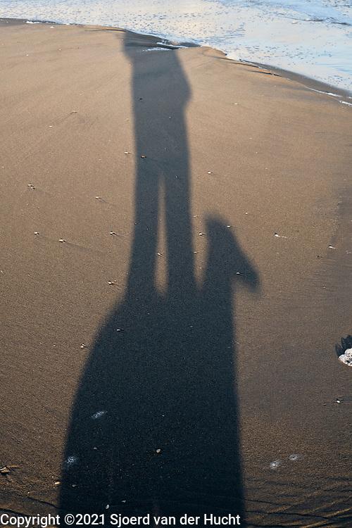 Shadow selfie with a dog photobombing on the beach.   Selfie met shaduw van mijzelf en een passerende hond op het strand.