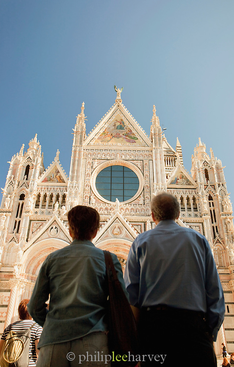 Tousists admire the decorated facade of the Duomo di Siena, the Cathedral of Siena, a Roman Catholic church in Siena, Tuscany, Italy
