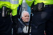 Phil Kingston, 83 is arrested as  climate change protest group Extinction Rebellion stage a protest at London City Airport during day four of two weeks of planned demonstrations on 10th October, 2019 in London, Untited Kingdom. Extinction Rebellion is demanding that governments drastically cut carbon emissions.
