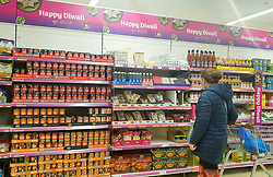 © Licensed to London News Pictures. 09/10/2020. London, UK. A shopper wearing a face mask views items for Diwali as Sainsbury's stock for the Festival of Light. This year Diwali falls on Saturday, 14 November. Diwali is the five-day festival of lights, celebrated by millions of Hindus, Sikhs and Jains across the world. It's a a festival of new beginnings and the triumph of good over evil, and light over darkness. Photo credit: Dinendra Haria/LNP