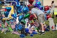 Matthew Saia in front of a cross he made at work and added to the makeshift memorial for the police officers killed in Baton Rouge. Three of the six officers shot were killed and another remains in criticial condition. The memorial in front of the  B-Quik gas station on Airline Hwy and continues to grow.