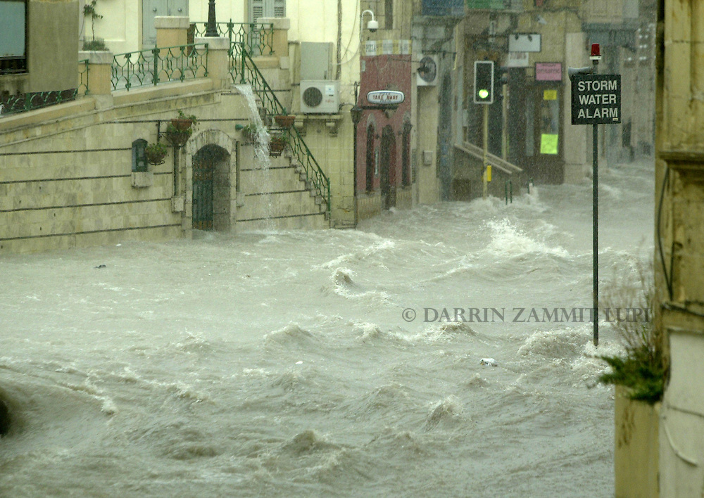 Flood waters rush through the main street in the town of Birkirkara in central Malta, June 4, 2007.  Rainfall that was as heavy as it was rare turned many of Malta's streets into torrents of raging waters on Monday, carrying away cars and flooding ground floor residences but causing no injures, civil protection officers said..REUTERS/Darrin Zammit Lupi (MALTA).MALTA OUT