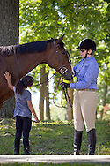 Middletown, New York - A female rider, at right, watches a young girl pet her horse at the 70th annual Middletown Rotary Horse Show at Fancher-Davidge Park on Sept. 8, 2013.