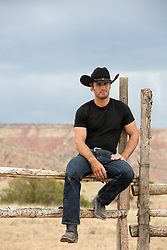 hot cowboy sitting on a rustic fence on a ranch