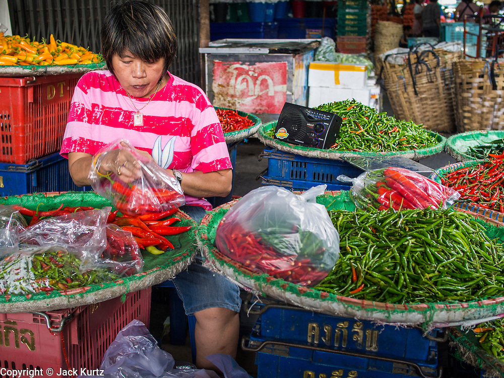 01 APRIL 2014 - BANGKOK, THAILAND: A chili vendor in the Bangkok flower market. The Yodpiman Flower Market (also called Pak Khlong Talat) is being renovated and gentrified. The market opened in 1961 and has been a Bangkok landmark for more than 50 years, is being turned into a high end mall. Many of the flower and vegetable vendors in the market may be forced out.    PHOTO BY JACK KURTZ