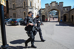 Windsor, UK. 17th April, 2021. Armed police officers from Thames Valley Police conduct a security patrol through the town centre on the day of the funeral of the Duke of Edinburgh. The funeral of Prince Philip, Queen Elizabeth II's husband, is taking place at St George's Chapel in Windsor Castle, with the ceremony restricted to 30 mourners in accordance with current coronavirus restrictions.