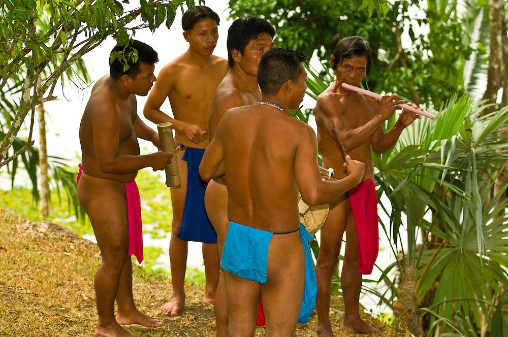 Embera Indian men in loin cloths play instruments in their village at Ellapuru, Chagres River, Soberania National Park (near the Panama Canal), Panama