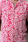 close up person wearing a bright flowery design shirt