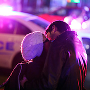 A kisses in front of police cars and flashing lights celebrating on U street in Washington DC after Barack Obama was announced the winner of the 2012 presidential elections.