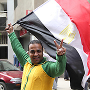 On his was to Cairo's Tahrir Square, a young protestor waves the Egyptian flag enthusiastically and gives the peace sign to passers by.
