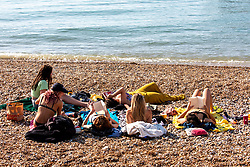 "© Licensed to London News Pictures. 14/09/2020. Sussex, UK. Sunbathers enjoy the hot sunshine this afternoon on Brighton Beach while keeping to the ""Rule of Six"" as a mini-heatwave hits England this week with highs of 29c. Prime Minister Boris Johnson announced last week that gatherings of more than six people will be banned from today in the hope of reducing the coronavirus R number. The Rule of Six as it is known, has already become unpopular with MPs and large families for being too strict. Photo credit: Alex Lentati/LNP"